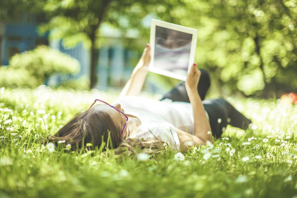 Woman looking at image while lying in the grass.