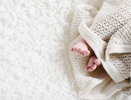 a newborn wrapped in a knit blanket