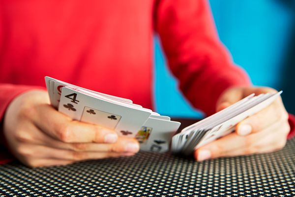 Child shuffling a deck of cards.