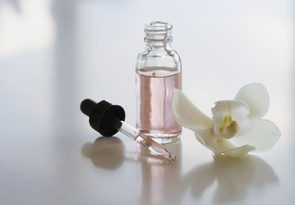 flower and bottle of essential oil perfume