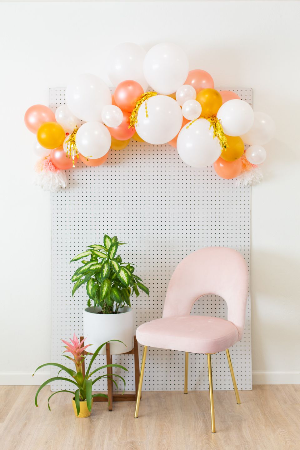 DIY balloon arch over a pink chair and by a plant in a mid-century modern planter