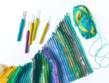 Bright crochet hooks and ball of yarn on white background.