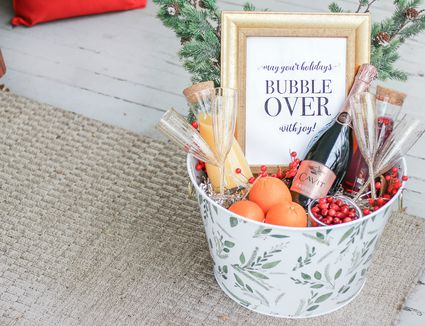 Themed gift basket with orange juice, champagne, cranberries and oranges.