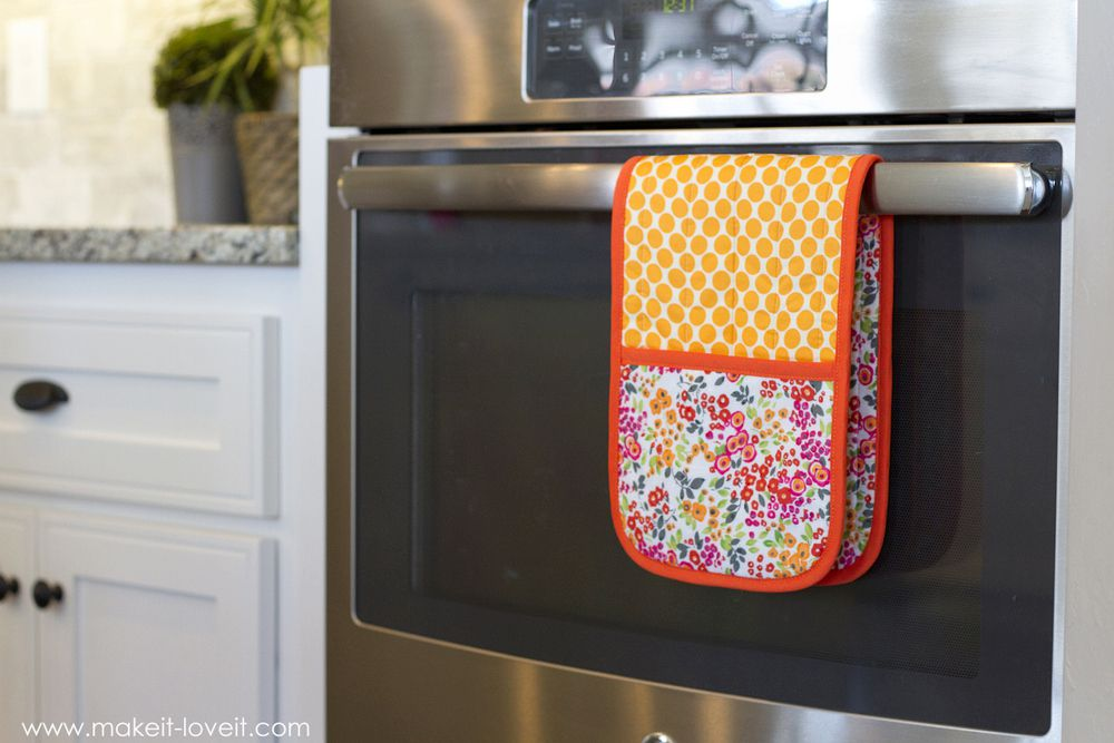 A double pot holder hanging on an oven