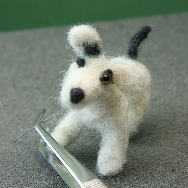 A 2mm glass eye on wire is attached through the head of a dollhouse scale miniature felt dog.