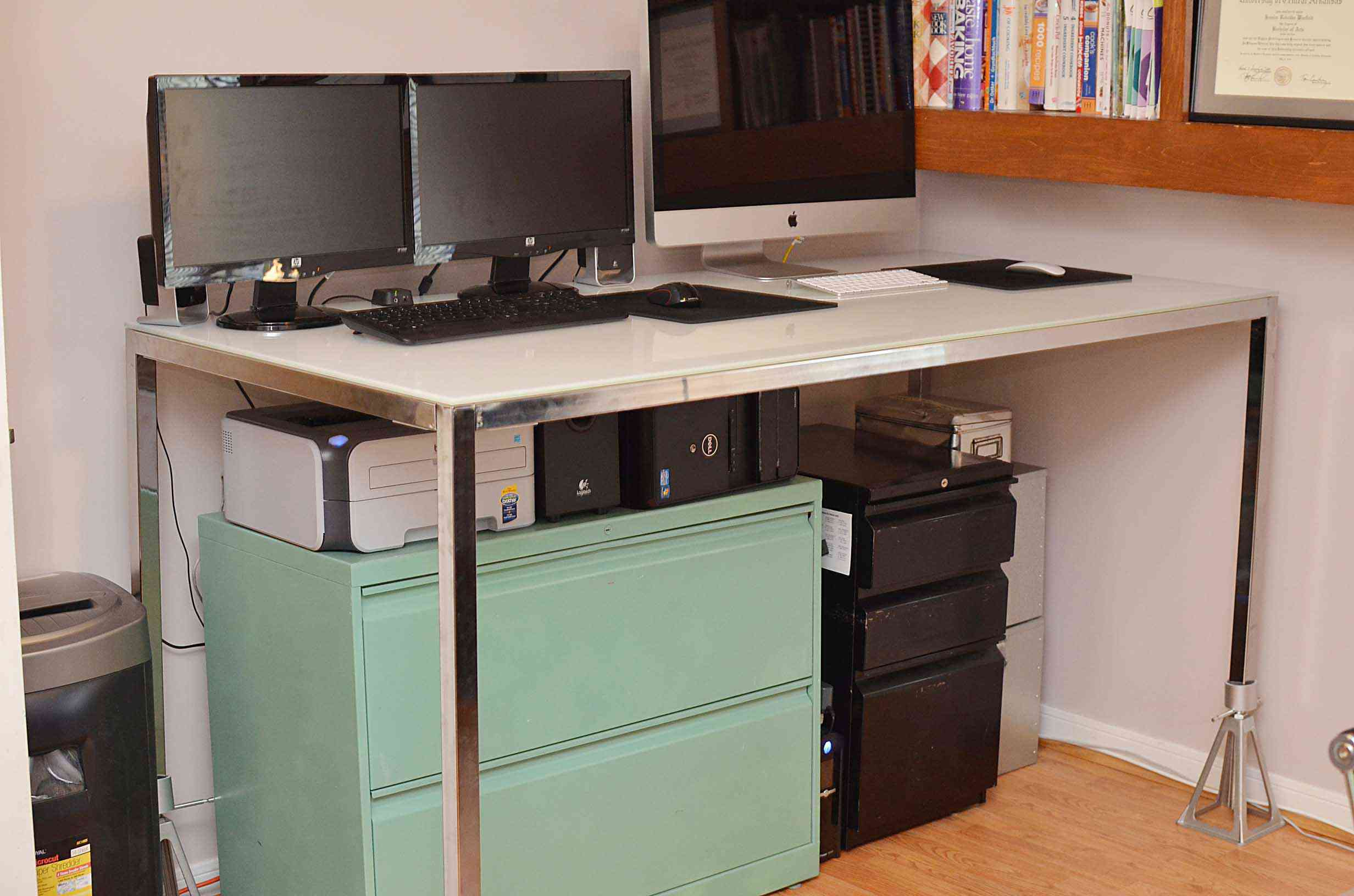 A tall standing desk with three monitors and a file cabinet underneath.