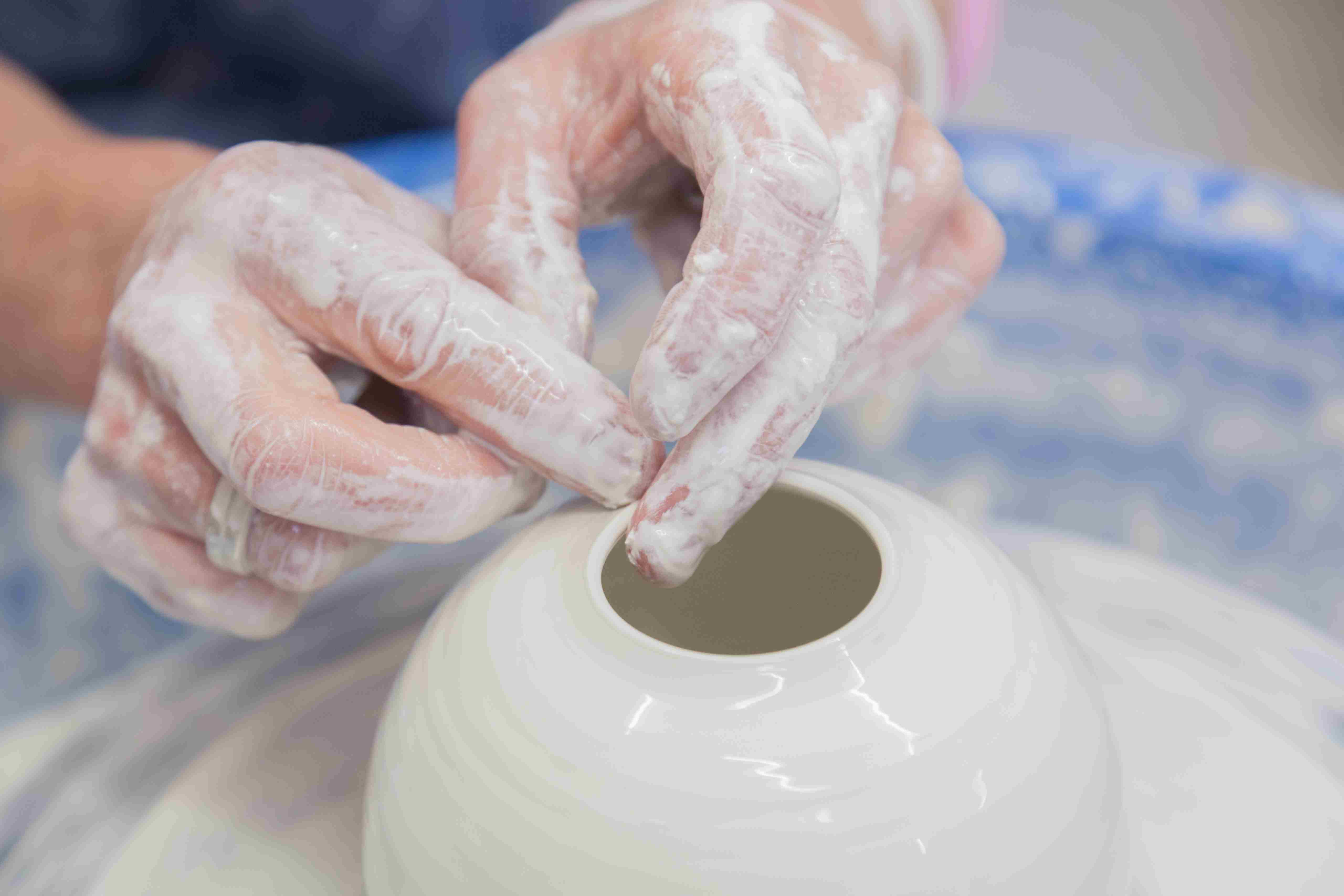 Close up of woman making pot on potter's wheel