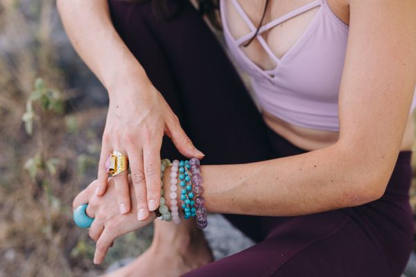 Female hands touching each other wearing several rings and bracelets from precious stones and yoga pants