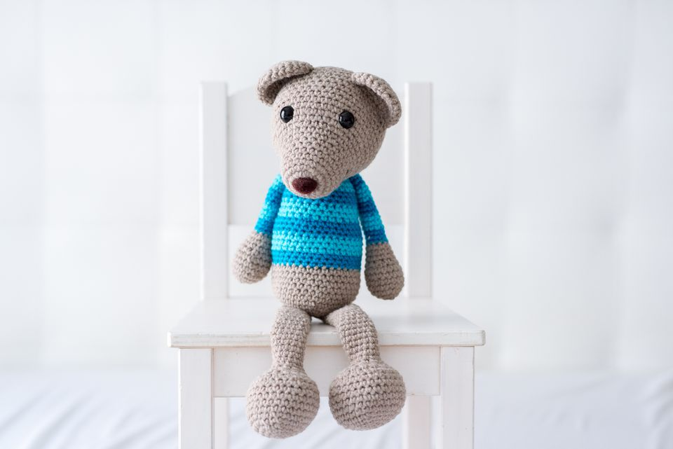 Handmade crocheted teddy bear with a striped shirt