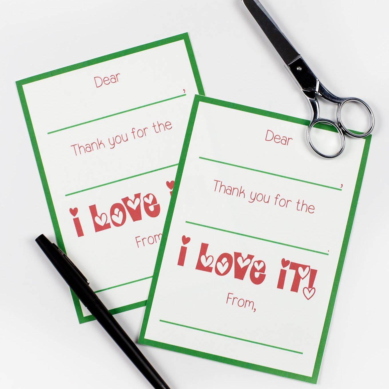 Two green and red Christmas thank you cards on a table