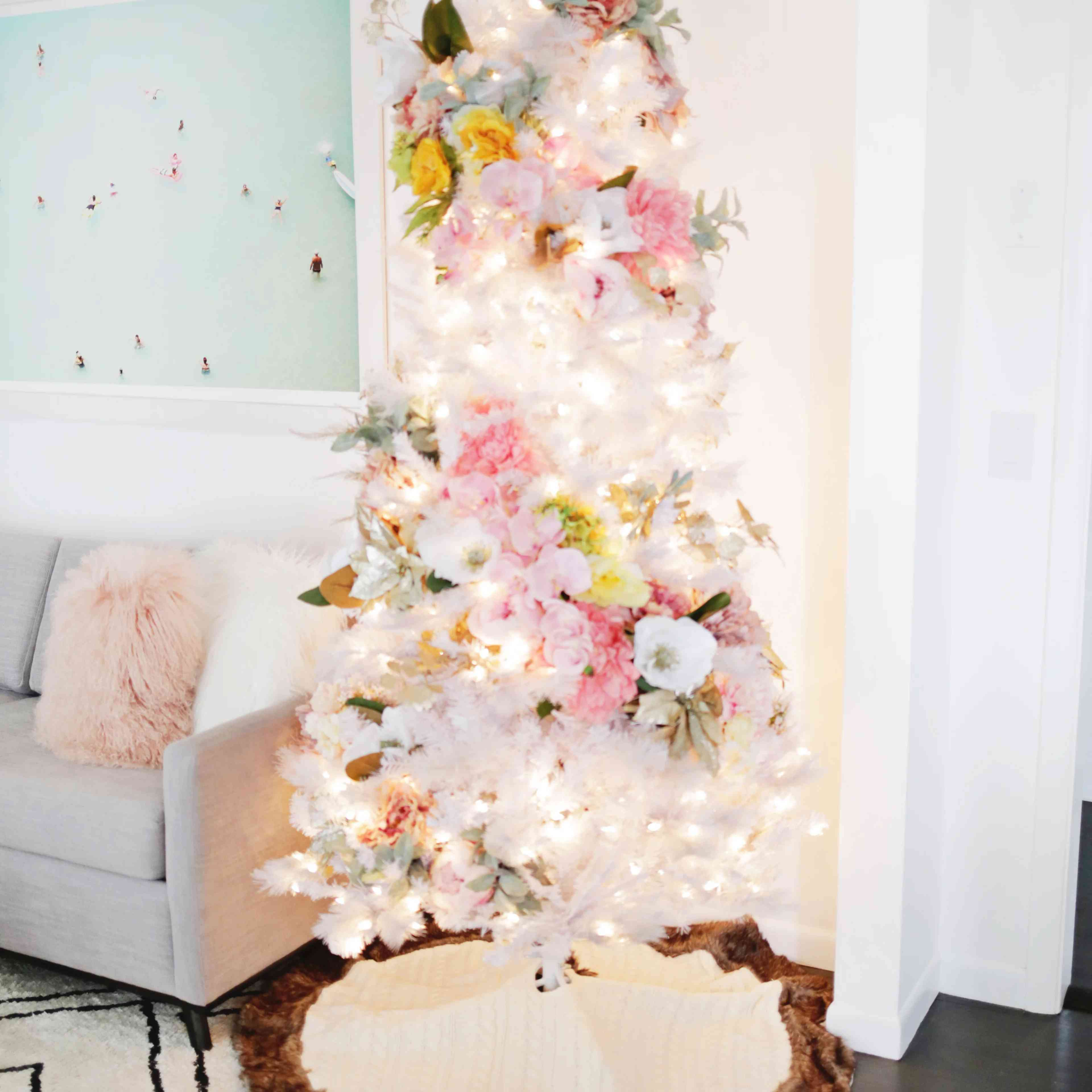 A white Christmas tree decorated with flowers.