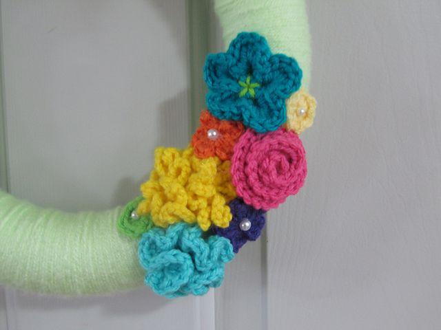 Pretty flowers added to a yarn wrapped wreath form