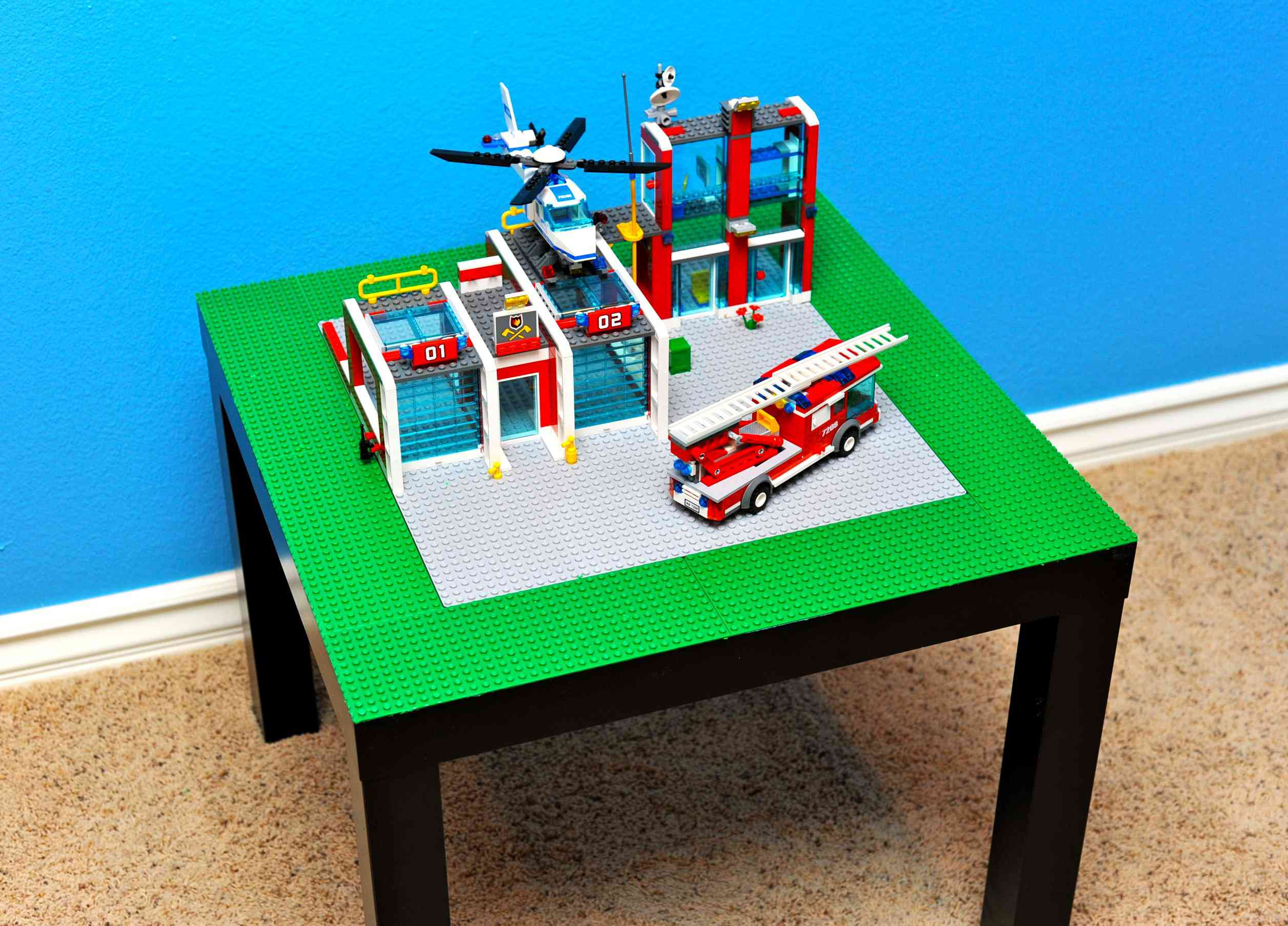 A lego table with a lego fire station built on top