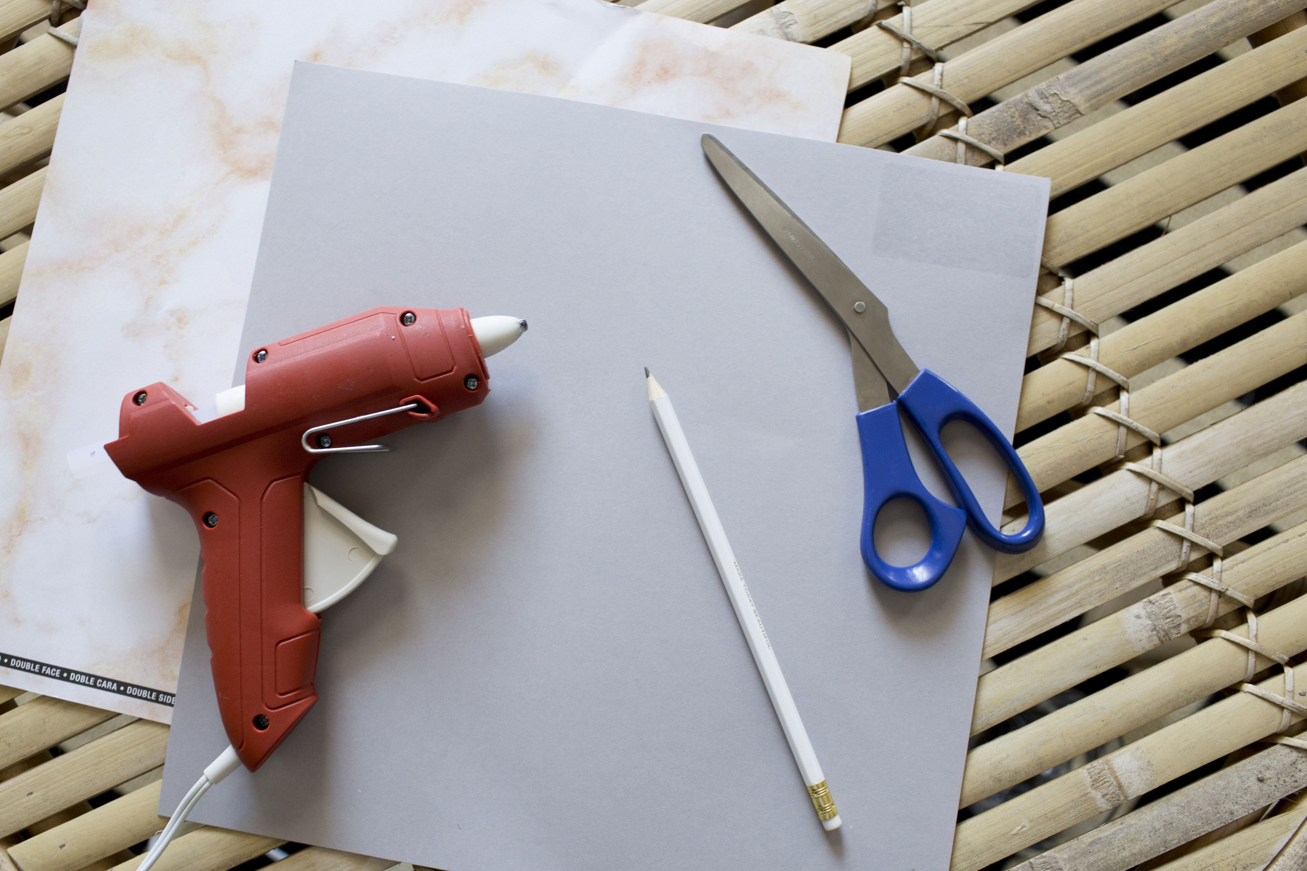 Hot glue gun, scissors, paper, and pencil all on a table.