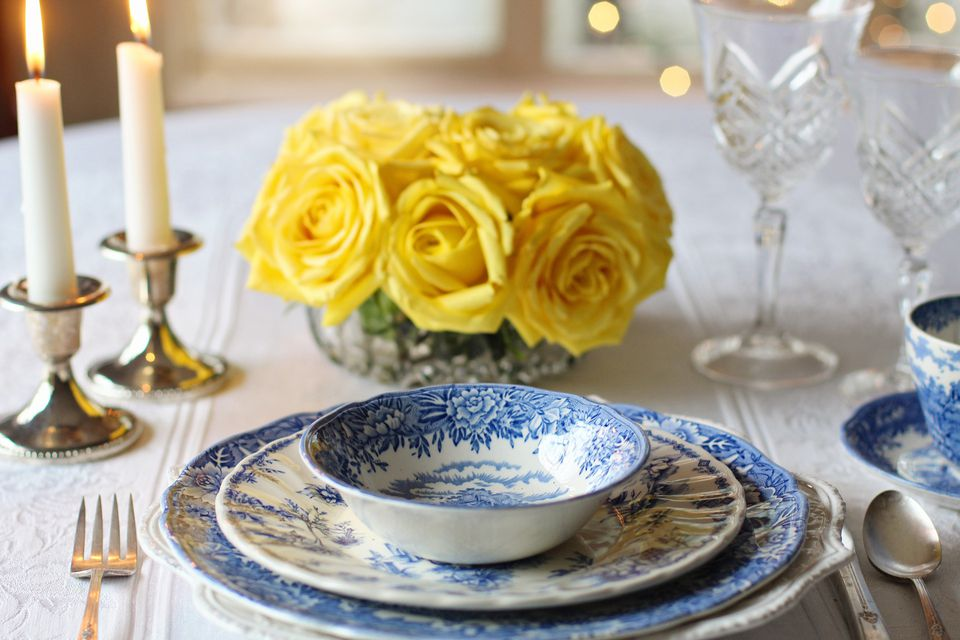 Place setting with vintage dinnerware, arrangement of yellow flowers, and lit candles..