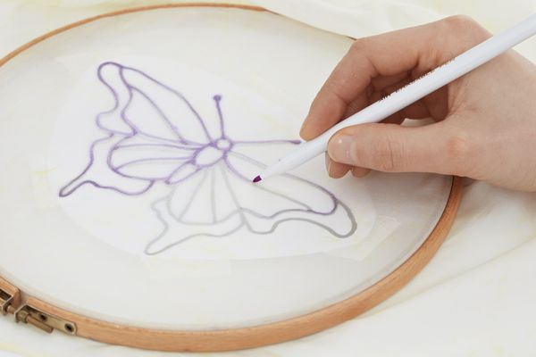 Tracing over lines of butterfly motif on silk scarf secured to embroidery hoop.