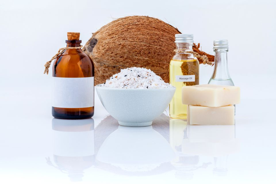 Close-Up Of Coconut With Soap And Massage Oil On White Background