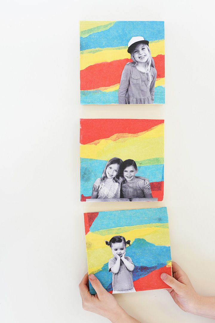 Person hanging tissue paper collage wall art