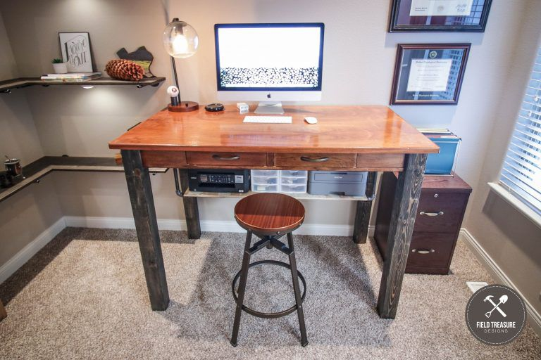DIY sturdy wooden standing desk with a stool in front of it and a mac on top.