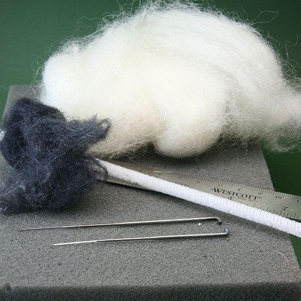 Wool and silk fibers, felting needles and a foam mat used to make scale miniature felted dogs.