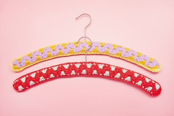 High angle view of handmade decorated coathangers with crocheted design on pink background