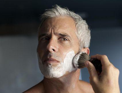 Mature man lathering face before shaving