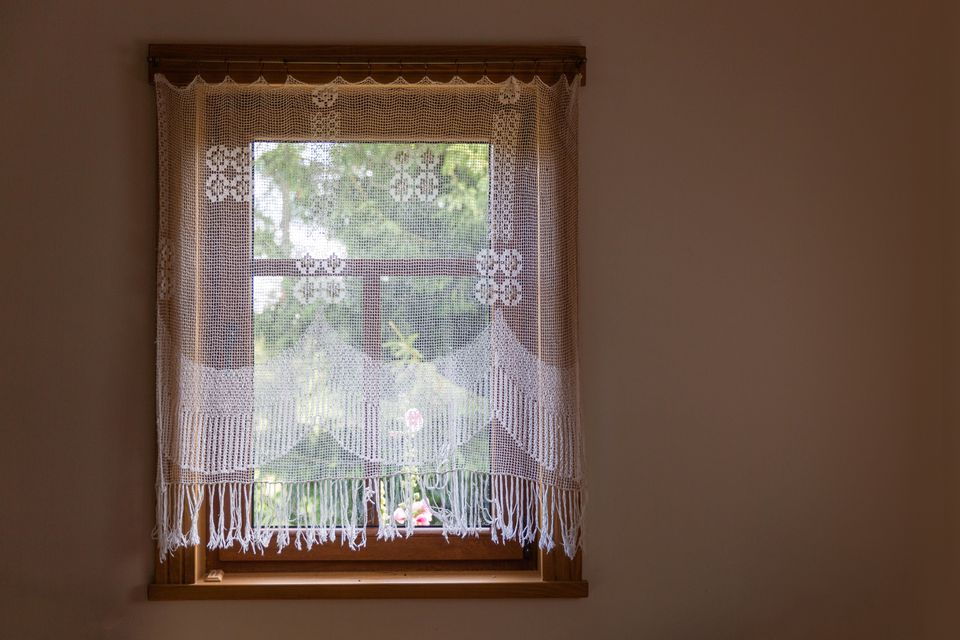 Folk crochet curtains on the wooden window