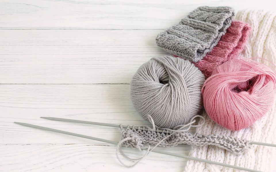 Grey and pink knitting wool and knitting needles on white wooden background.