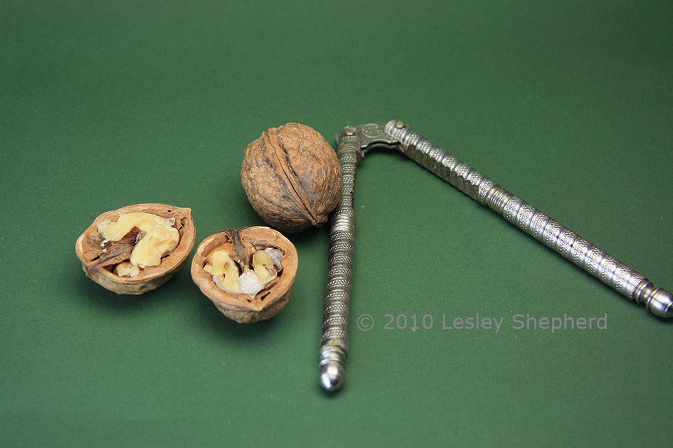 English walnuts split in half with a two-arm nutcracker