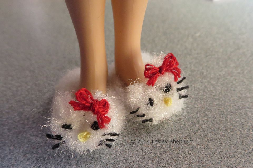 Fuzzy animal slippers on the feet of a dollhouse scale doll.