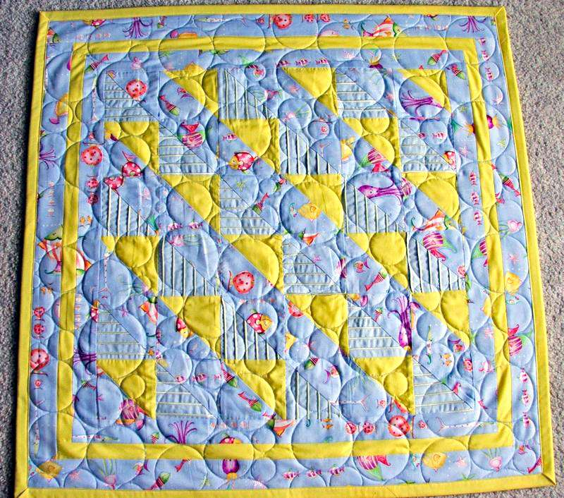 Blue and yellow fishy baby quilt.