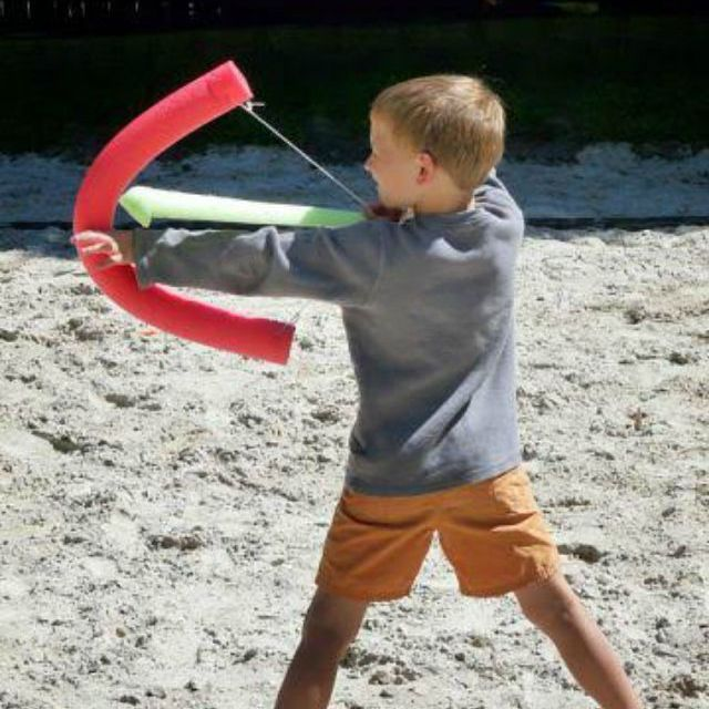 Boy using red noodle bow and green noodle arrow.
