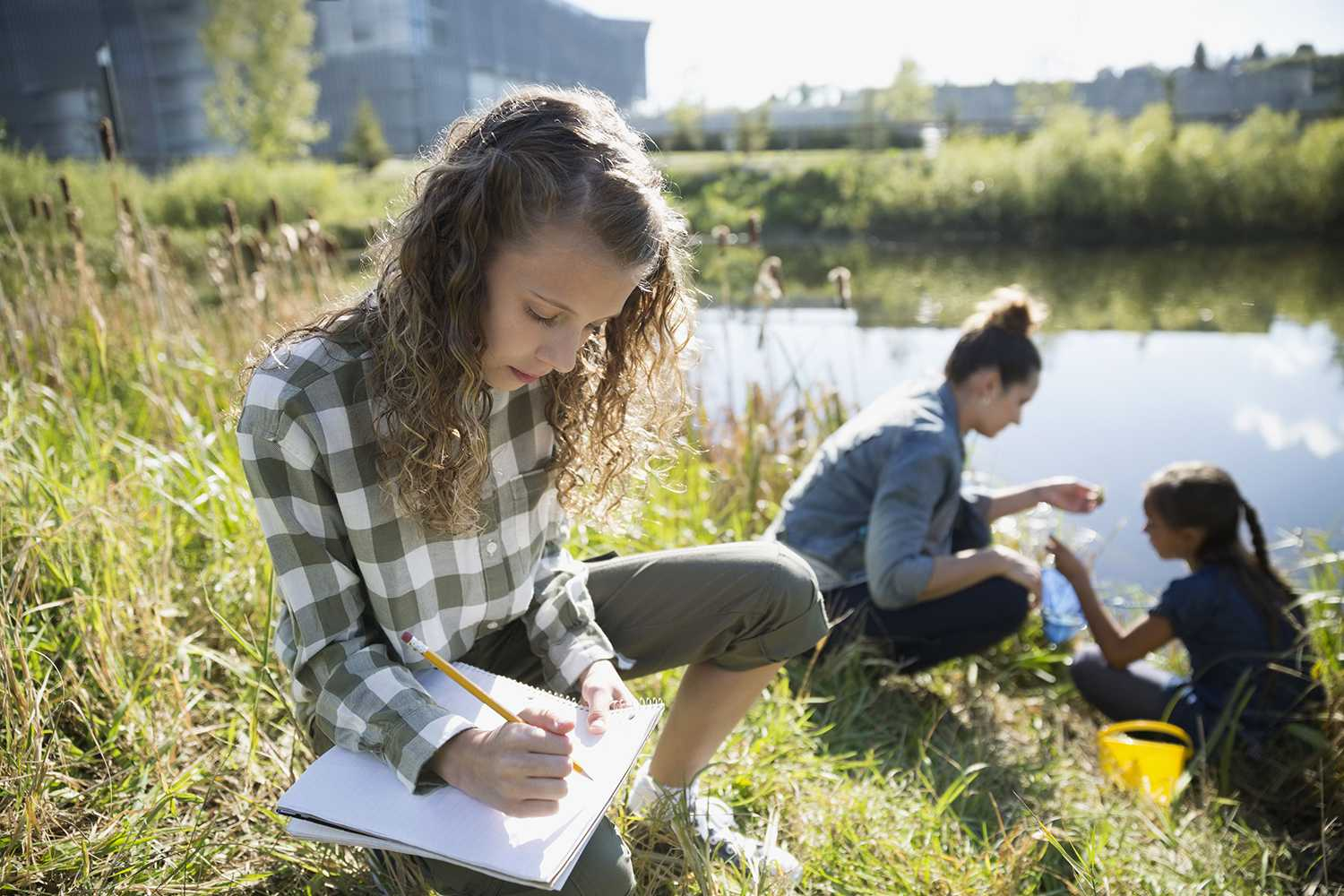 girl taking notes in a field by a pond