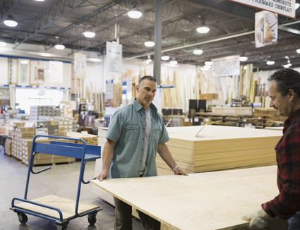 Men carrying plywood in home improvement store