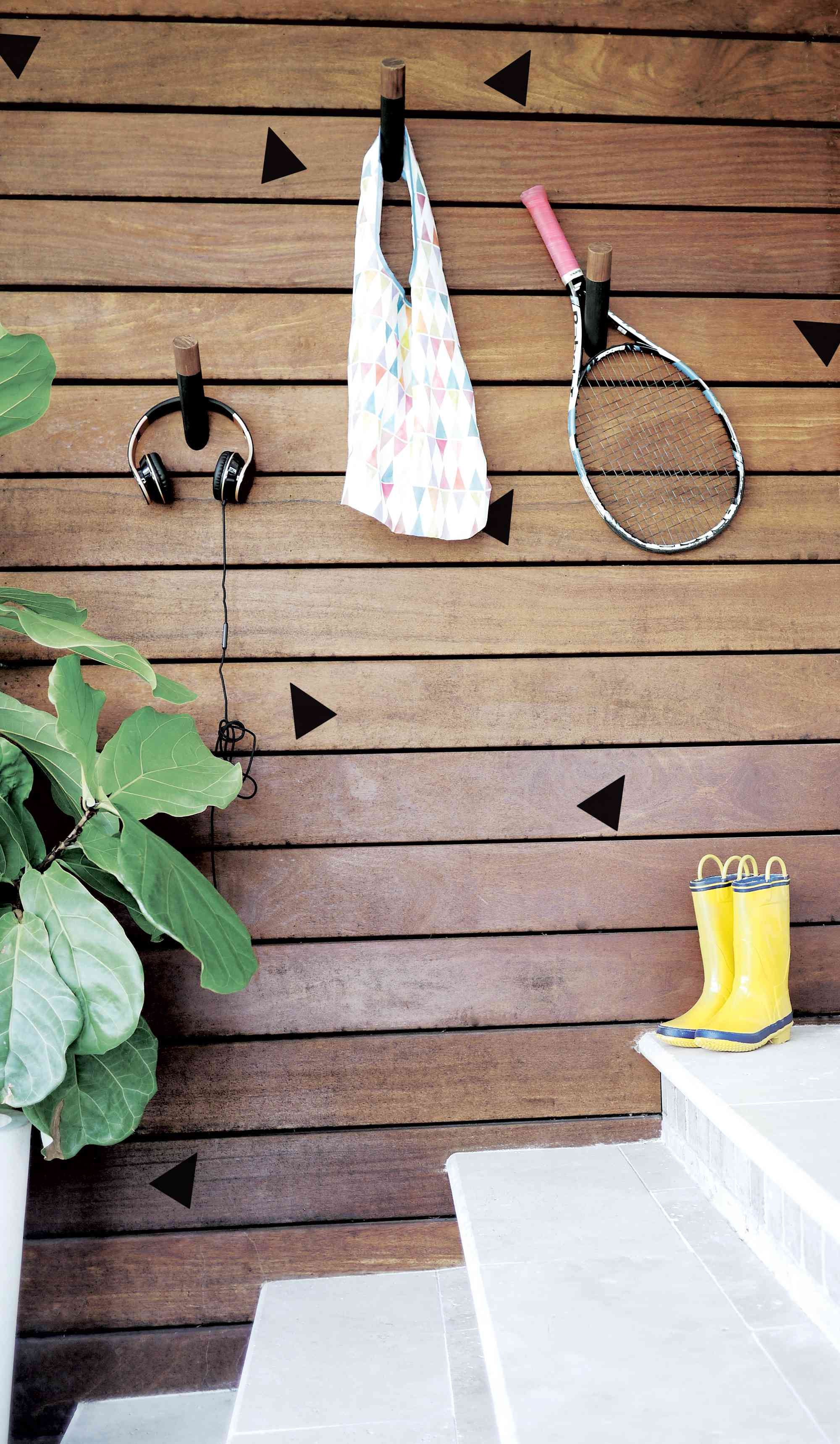 A bag, headphones and a tennis racket hanging on wall hooks on a wood wall.