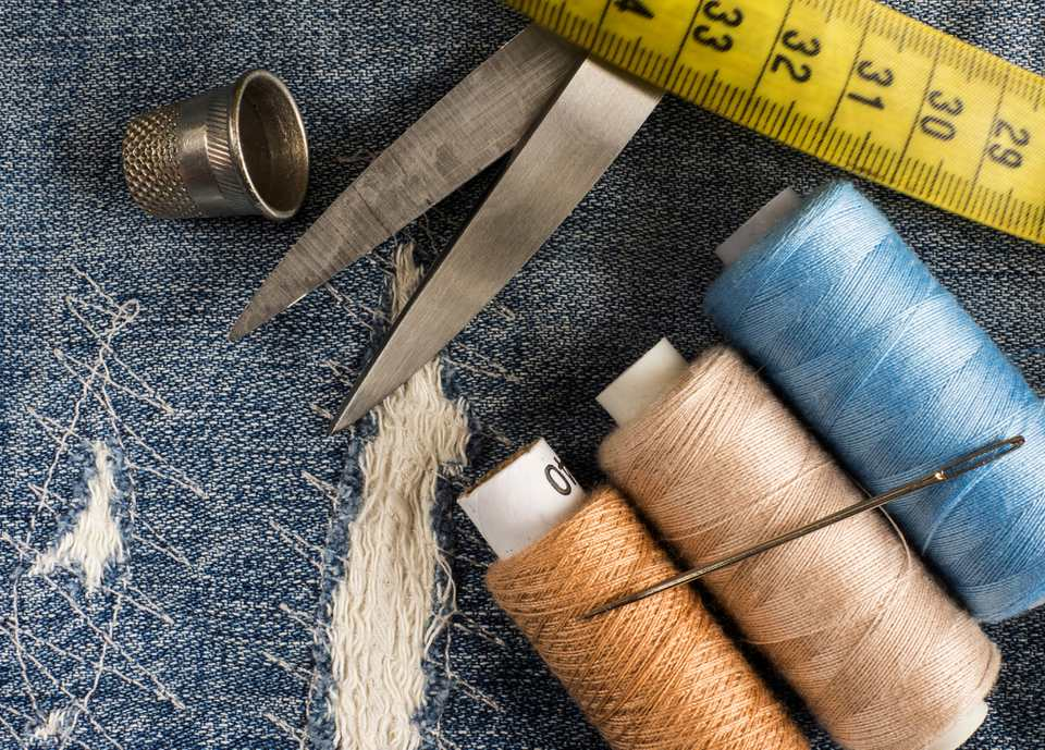 Sewing materials arranged on a pair of pants.