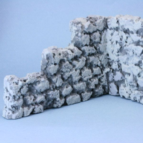 A faux stone wall made from styrofoam bead board with three shades of grey applied to mimic stone.