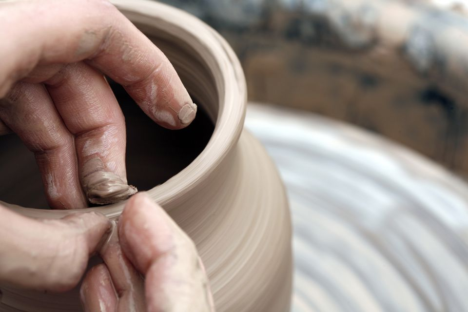 Hand molding a clay container on a pottery wheel