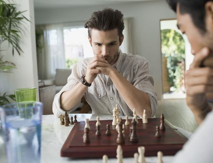 Focused men playing chess at table
