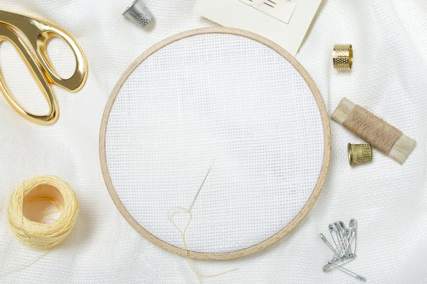 Closeup of wooden embroidery frames, scissors, threads, thimbles, needles, and clean white fabric for embroidering.Empty space for hobby design